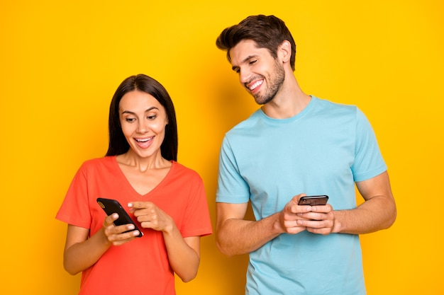 Photo of two funny guy lady people couple hold telephones showing finger positive comments reposts excited wear casual blue orange t-shirts isolated yellow color wall