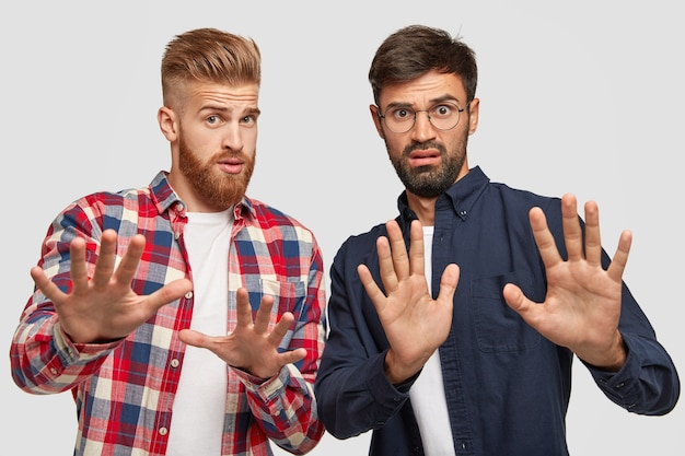 Photo of two guys stretch hands , have displeased expression