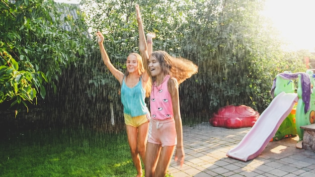 Photo of two happy laughing sisters in wet clothes dancing under water droplets from garden hose at garden. family playing and having fun outdoors at summer