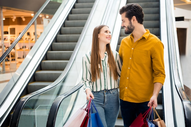 Photo of two people cheer attractive lady handsome guy couple enjoy free time buy carry many bags moving down escalator shopping center hug look eyes wear casual jeans shirt outfit indoors