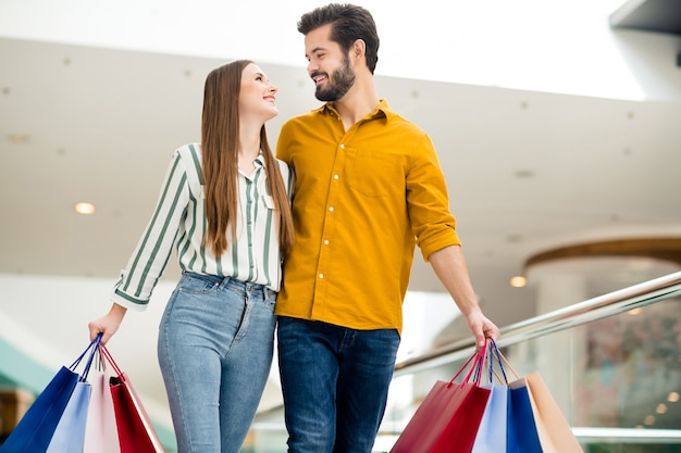 Photo of two people cheerful attractive lady handsome guy couple enjoy free time buy hold many bags walk shopping center hugging look eyes wear casual jeans shirt outfit indoors