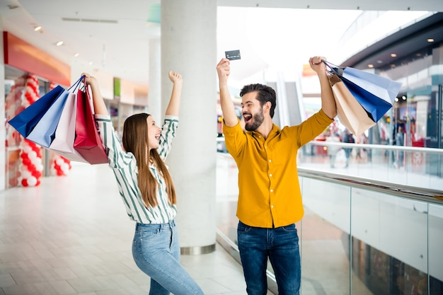 Photo of two people cheerful pretty lady handsome guy couple enjoy free time hold many bags walk shopping center raise hands use credit card discounts wear casual jeans shirt outfit indoors