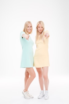 Photo of two pretty ladies pointing at the front. standing over white wall.