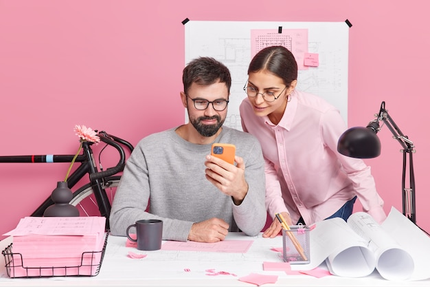 Photo of two skilled woman and man designers work at new creative project see some examples of drawings in smartphone pose at workplace speak with each other enjoy collaboration. teamwork concept
