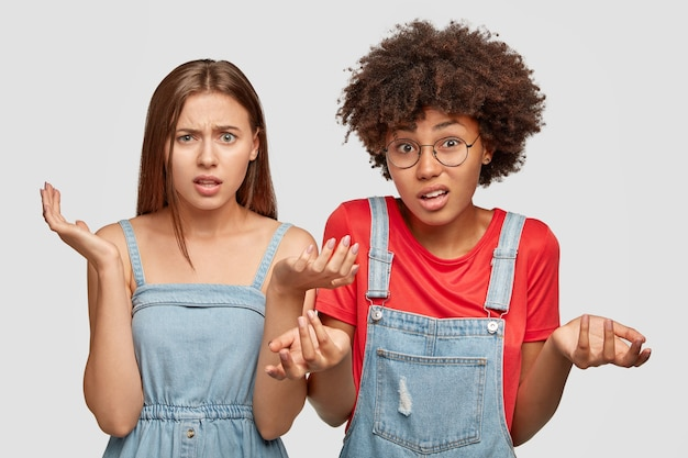 Foto di ragazze incerte di razze diverse, esprimono dubbi
