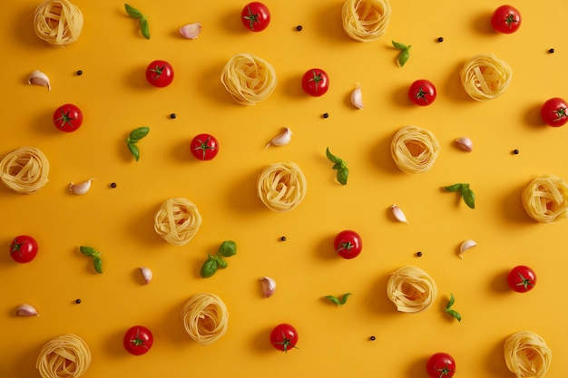 Photo of uncooked pasta nests lying around edible red tomatoes, garlic, peppercorns, basil on yellow background. cooking nourishing meal. italian traditional cuisine. big variety of products