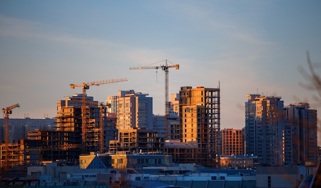 Photo of unfinished houses, cranes in evening