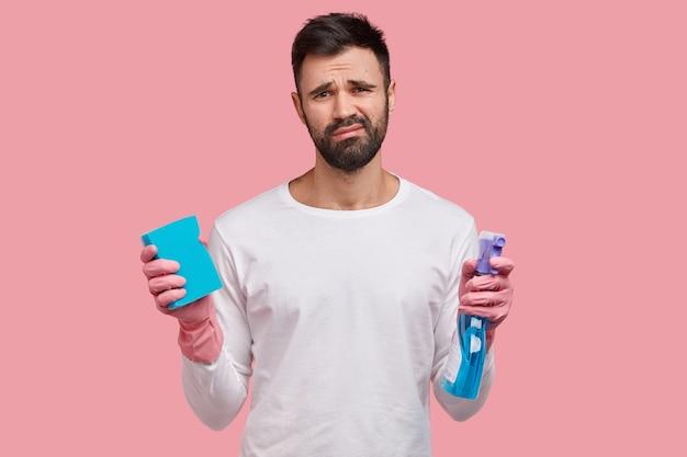 Foto di un uomo caucasico infelice con stoppie scure, vestito con abiti bianchi, detiene la scopa e lo spray di lavaggio, si prepara per le pulizie di primavera