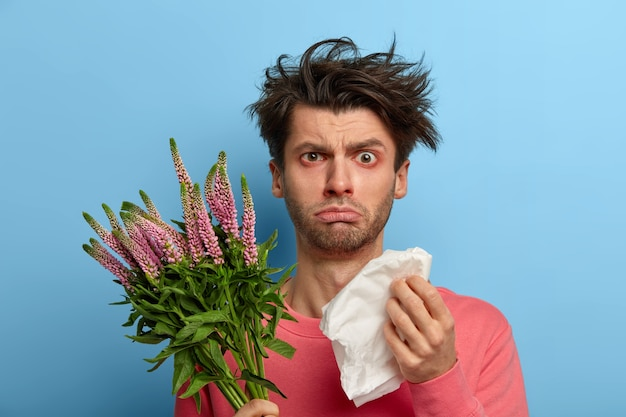 Photo of unhappy sick young man has problems with health, rubs nose with paper tissue, suffers from sneezing and watery eyes, has allergy on seasonal spring plant, hypersensitivty to blossoming