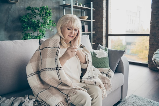 Photo of unhappy white haired aged granny caught cold sneezing napkins everywhere chaos holding thermometer sitting sofa divan covered plaid blanket living room indoors