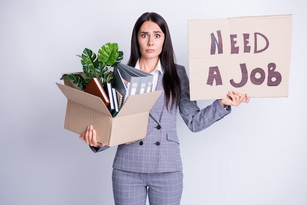 Photo of unhappy worker young dismissed lady financial crisis lost work hold carton box stuff fired quit hold placard banner search new opportunity formalwear isolated grey color background