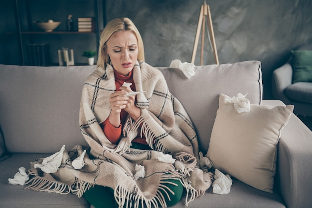 Photo of unhealthy pretty blond lady suffering flu caught cold paper napkins everywhere hold thermometer sitting couch covered plaid blanket living room indoors