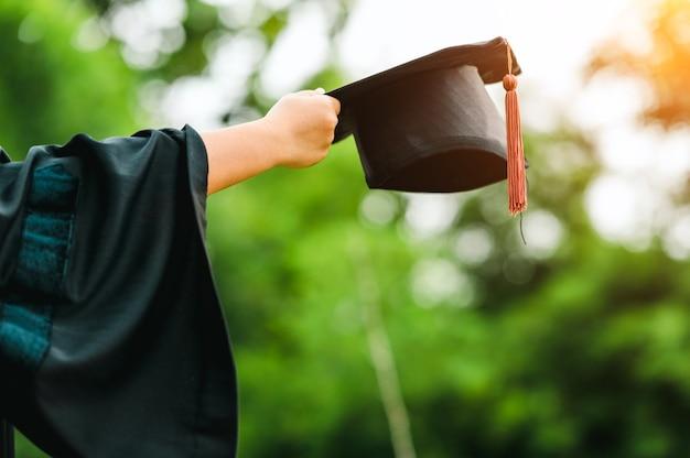 Behind photo of university graduate wears gown and black cap brown tassel