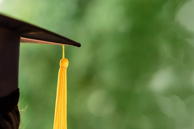 Behind photo of university graduate wears gown and black cap, yellow ribbon