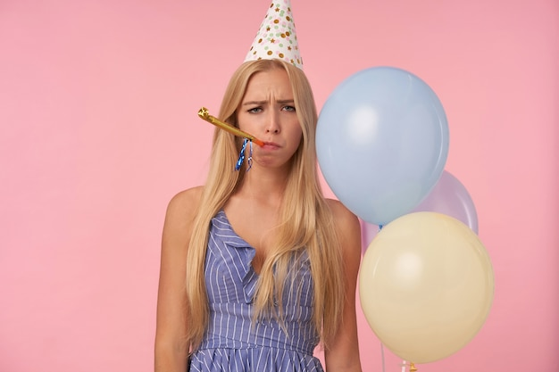 Photo of unpleased long haired blonde lady in blue summer dress and holiday cap blowing party horn casual over pink background, looking at camera with upset face and holding bunch of helium balloons