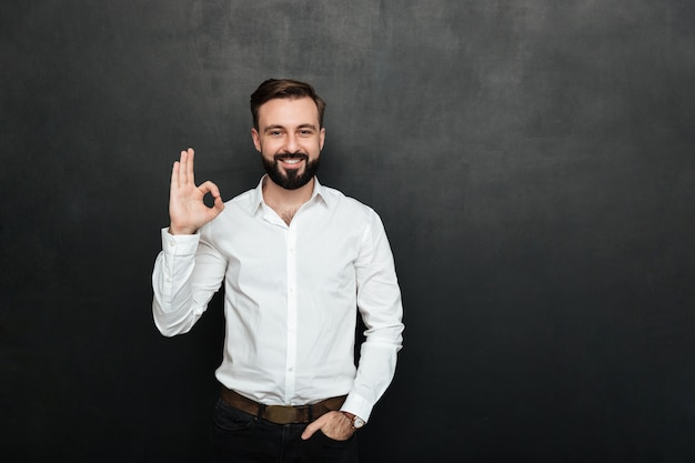 Photo of unshaved guy in office smiling and gesturing with ok sign expressing everything is alright, isolated over graphite