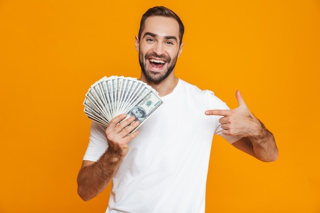 Photo of unshaved man 30s in casual wear holding bunch of money, isolated