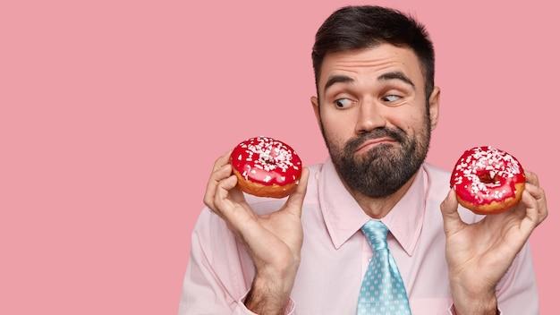 Foto di un uomo caucasico con la barba lunga vestito con abiti eleganti, esita se mangiare cibo spazzatura, tiene in mano le ciambelle