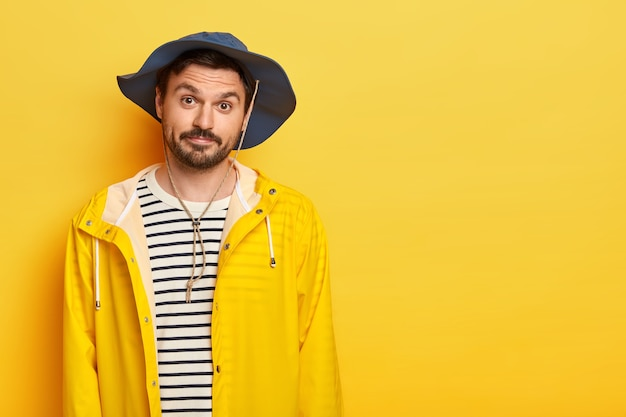 Photo of unshaven man has recreation time, going to fishing during weekend, wears hat and protective raincoat, looks with little surprisement, poses over yellow wall, free space