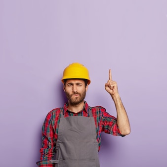 Photo of unshaven mechanical worker wears construction helmet and special uniform