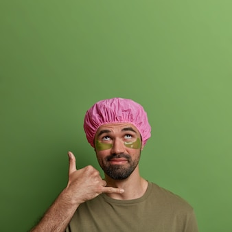 Photo of unshaven young man makes call me gesture, concentrated above, wears bathing cap, applies green patches under eyes for reducing wrinkles, has hygienic and spa treatment, cares about skin