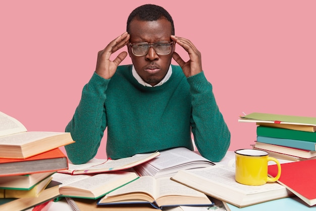 Photo of upset black young male worker has headache, works hard, reads literature, suffers from migraine