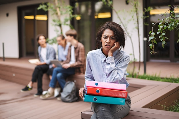 Photo of upset lady sitting on bench with colorful folders and sadly