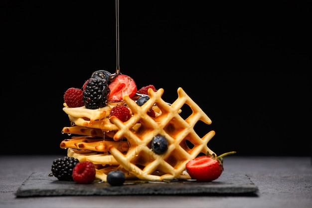 Photo of viennese wafers with berries pouring honey on black empty background in studio