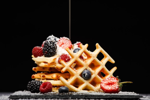 Photo of viennese wafers with raspberries, strawberries sprinkled with powdered sugar, with honey on black empty background in studio