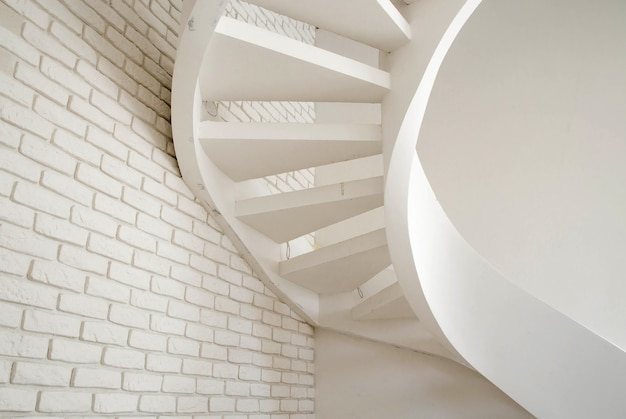 Photo of a wall of white brick and a spiral staircase in the house