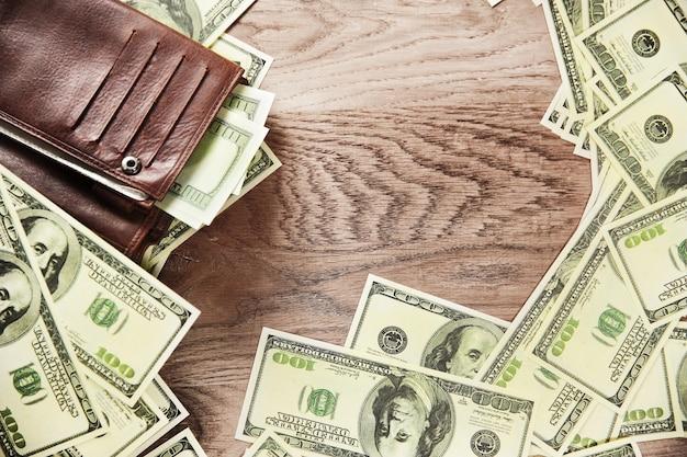 Фото кошелек и банкноты долларов на деревянном фоне