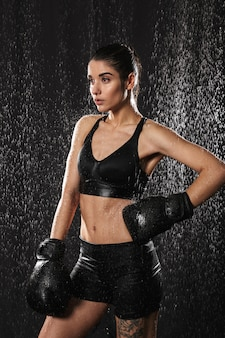 Photo of wet attractive woman with hair in ponytail putting arm in boxing gloves on waist and looking aside under water drops, isolated over black background
