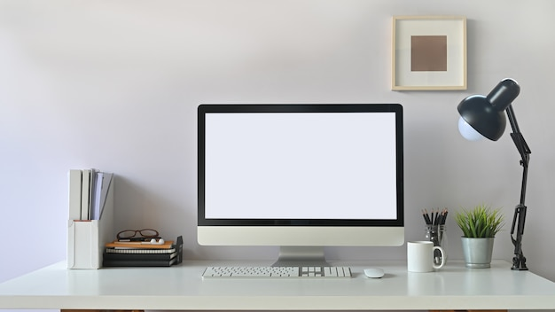 Photo of white blank screen computer  and office equipment is on the table. modern working desk concept.