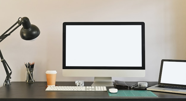 Photo of white blank screen computer and white blank screen laptop putting on the table together including lamp, coffee cup, mouse pencil holder and personal equipment. modern working desk concept.