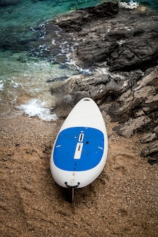 Photo of white and blue surfboard lying on sand beach next to wavy sea