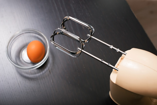 Photo of a white kitchen mixer standing on a black table near an egg.