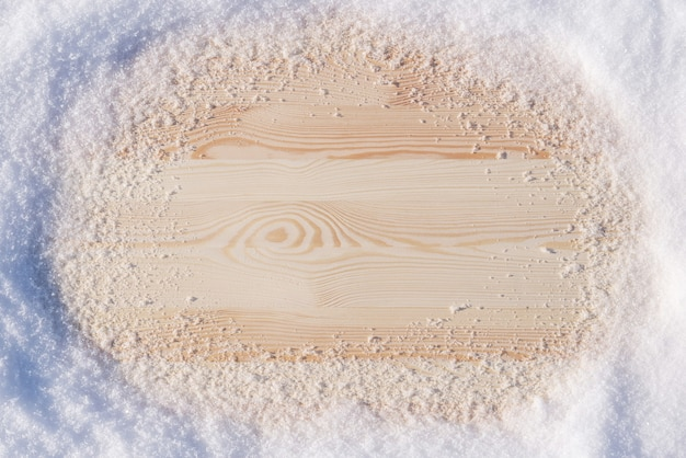Фото с копией пространства деревянного стола с естественным снегом вокруг под ярким зимним солнцем