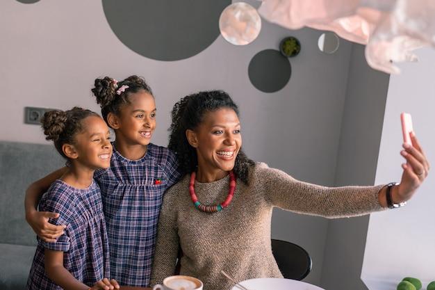 Фото с дочерьми. привлекательная стильная красивая сияющая мама в ярком колье фотографируется с дочерьми