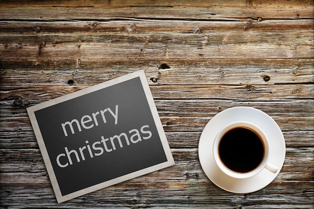 Photo with the text merry christmas lies on a wooden table with a cup of coffee