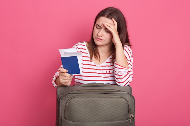 Photo of woman dressed striped shirt on pink background, looks tired and exhausted
