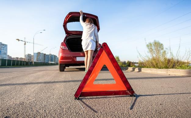 Photo of woman looking in trunk of broken car