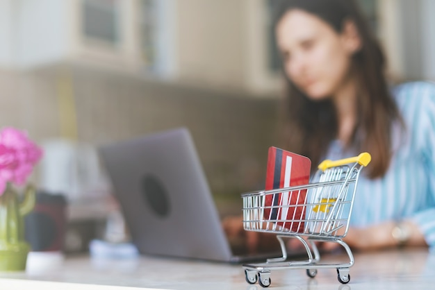 Photo of woman making online shopping with trolley cart.