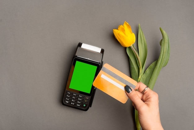 Photo of woman paying with credit card by paypass near yellow tulip