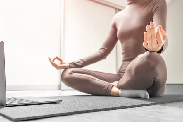 Photo of woman practicing yoga training online at home with laptop.
