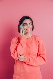 Foto di donna sorridente mentre parla sullo smartphone isolate su sfondo rosa