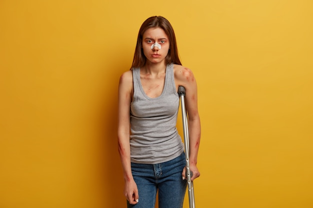Photo of woman victim of accident has nose breakage, poses with crutch, cannot walk by herself, gets concequences of careless driving, dressed in vest, jeans, has abrasion and bruises on skin
