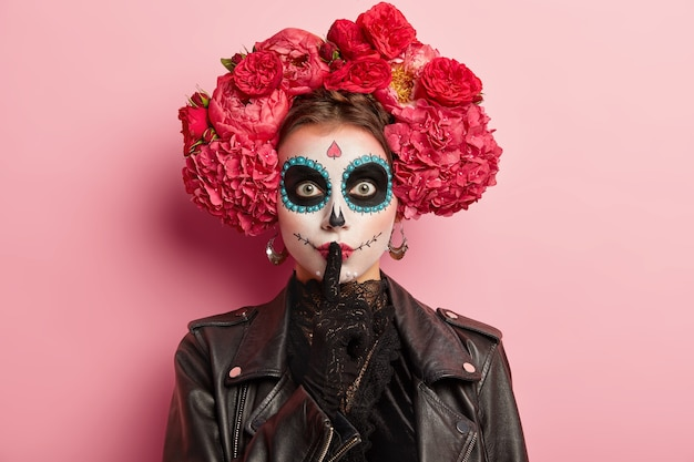 Photo of woman with traditional makeup and flowers on hair, makes hush gesture, keeps index finger over painted lips, prepares for awful death party, dressed in black outfit, isolated on pink