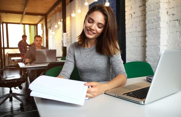 Фото женщина, работающая с новым запускаемым проектом в современном лофте. блокнот универсального дизайна на деревянном столе. эффект заката
