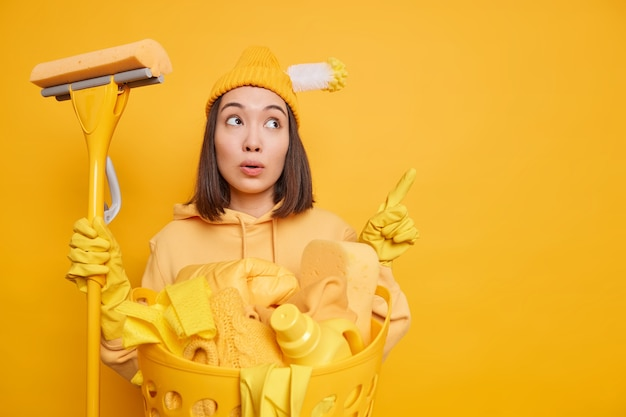 Photo of wondered asian woman points away on copy space demonstrates something poses with cleaning supplies does laundry during busy saturday isolated over yellow background. housework concept