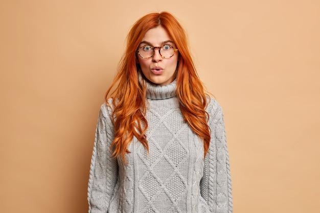 La foto della stupita donna rossastra fissa gli occhi spalancati trattiene il fiato rimane senza parole ansiosa di sentire notizie incredibili indossa occhiali trasparenti e maglione grigio lavorato a maglia.
